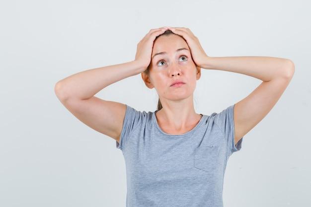 Jovem fêmea segurando as mãos na cabeça em uma camiseta cinza e olhando perplexa, vista frontal.