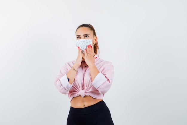 Jovem fêmea segurando as mãos nas bochechas em camisa, calça, máscara médica e olhando pensativa. vista frontal.