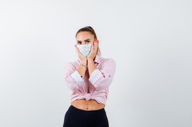 Jovem fêmea segurando as mãos nas bochechas em camisa, calça, máscara médica e parecendo perplexa. vista frontal.