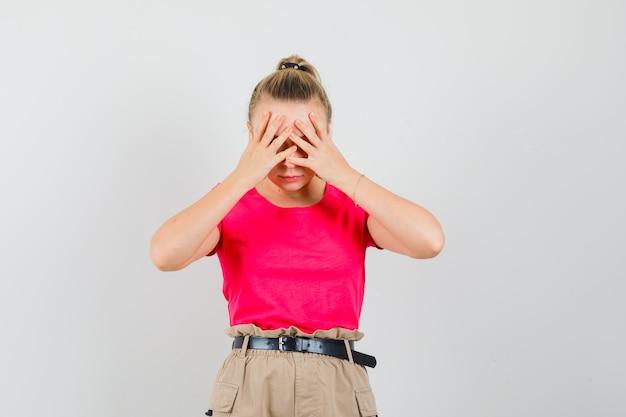 Jovem fêmea segurando as mãos no rosto em t-shirt, calça e olhando desesperada. vista frontal.