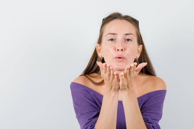 Jovem fêmea segurando as palmas das mãos para enviar beijo no ar em vista frontal da camisa violeta.