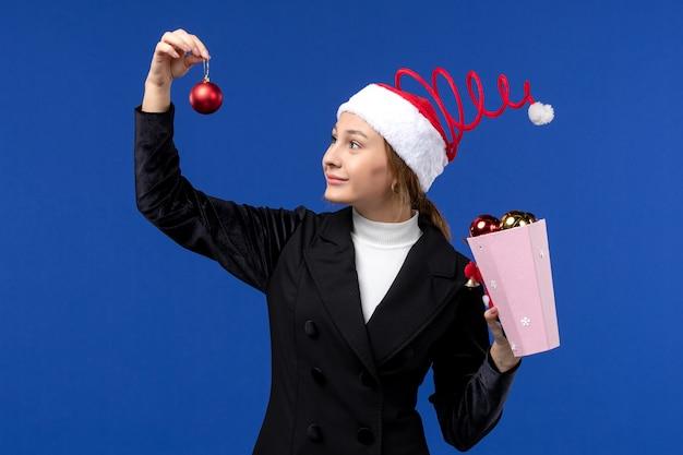 Jovem fêmea segurando brinquedos de árvore em fundo azul emoções azuis, férias de ano novo