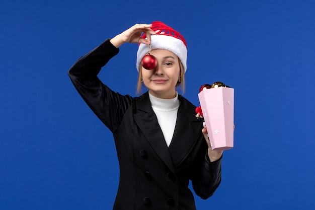 Jovem fêmea segurando brinquedos de árvore no fundo azul, emoção azul, férias de ano novo, vista frontal