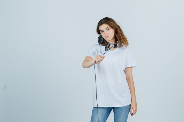 Jovem fêmea segurando fones de ouvido em t-shirt branca, jeans e olhando atraente, vista frontal.