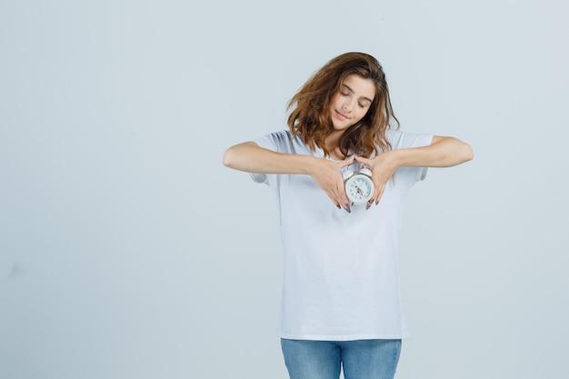 Jovem fêmea segurando o despertador em t-shirt branca, jeans e olhando graciosa, vista frontal.