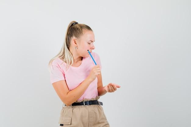 Jovem fêmea segurando o lápis e olhando para a mão em concha na t-shirt, vista frontal das calças.