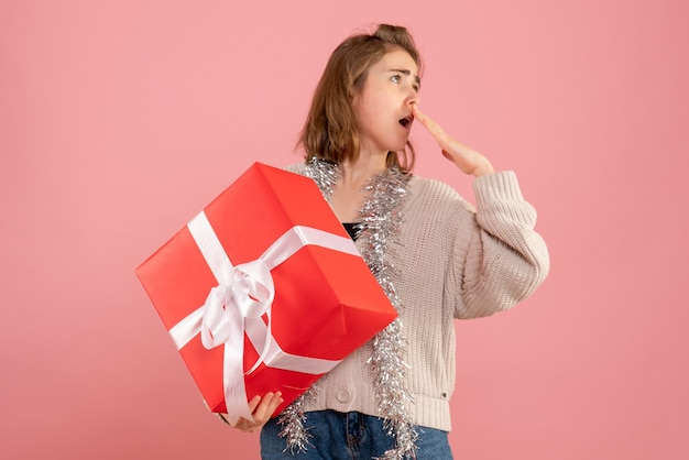 Jovem fêmea segurando o presente de natal nas mãos na rosa