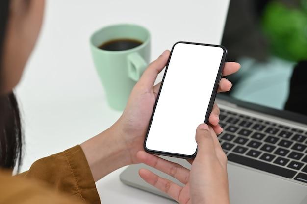 Jovem fêmea segurando o telefone móvel com tela vazia isolada