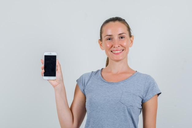 Jovem fêmea segurando o telefone móvel em t-shirt cinza e parecendo alegre. vista frontal.