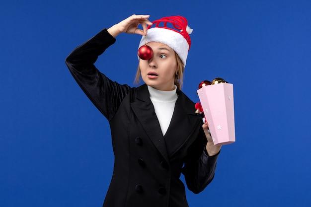 Jovem fêmea segurando os brinquedos da árvore no fundo azul, com as emoções do feriado de ano novo, vista frontal