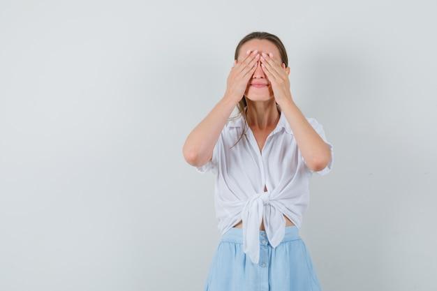 Jovem fêmea segurando os olhos com a blusa, saia e parecendo sonhadora