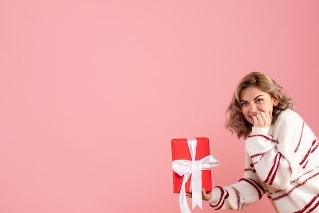 Jovem fêmea segurando presente rosa