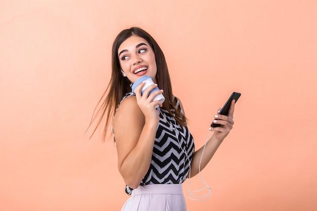 Jovem fêmea segurando smartphone e xícara de café