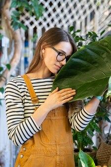 Jovem fêmea segurando uma folha verde relaxando depois do trabalho em uma estufa ou no jardim da casa