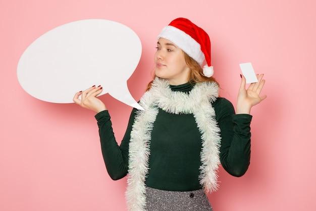 Jovem fêmea segurando uma grande placa branca e um cartão do banco no modelo de parede rosa, férias natal
