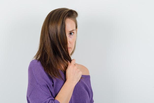 Jovem fêmea segurando uma mecha de cabelo na camisa violeta, vista frontal.