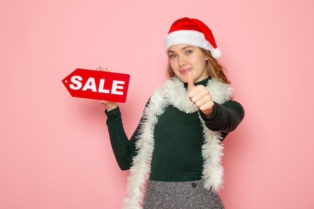Jovem fêmea segurando uma venda vermelha escrita na parede rosa natal ano novo compras moda emoção férias