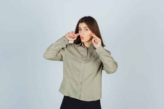 Jovem fêmea tapando as orelhas com os dedos, mantendo os lábios dobrados na camisa