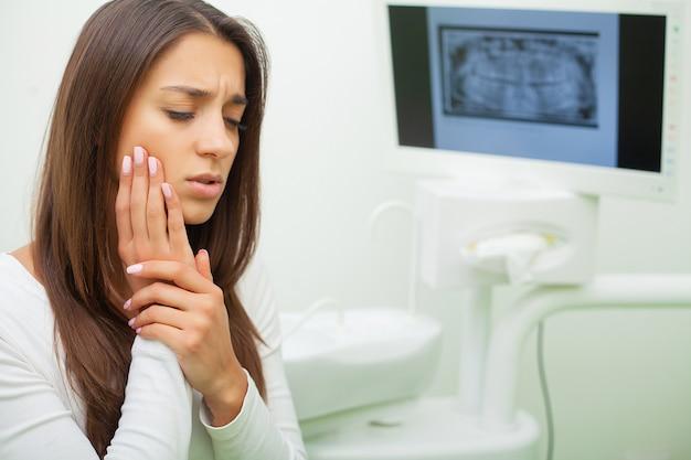 Jovem fêmea tendo dor de dente. mulher chateada no dentista. dor pulsante constante