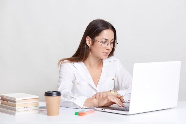 Jovem fêmea trabalhos administrativos no computador portátil, pesquisa informações na internet, vestida de bebida quente de bebidas brancas, usa livros para escrever papel de diploma, isolado sobre a parede branca