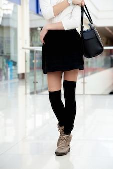 Jovem feminina caminhando de roupas na moda perto das pernas