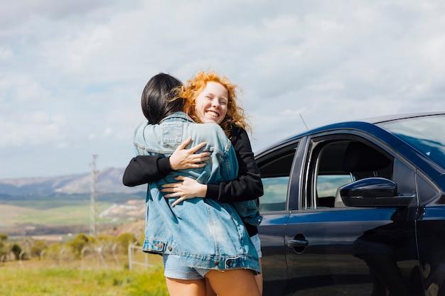 Jovem, femininas, abraçando, à margem estrada