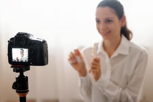 Jovem, femininas, blogger, com, câmera, dslr, vlogging, rewievs, cuidado corpo, produto, em, garrafa, modernos, online, trabalho, conceito