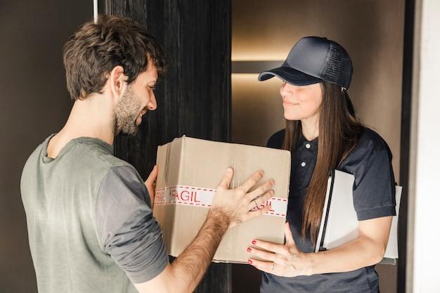 Jovem, femininas, courier, entregar, pacote, para, homem, casa