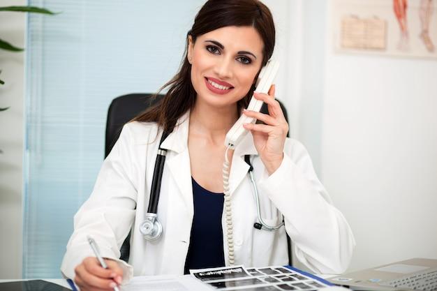 Jovem, femininas, doutor, trabalhando, em, escrivaninha escritório, e, responder, telefonema chama