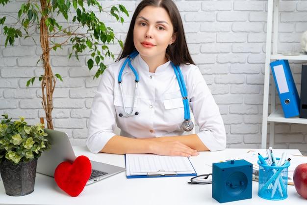 Jovem, femininas, médico, cardiologista, sentando, em, dela, escrivaninha, e, trabalhando