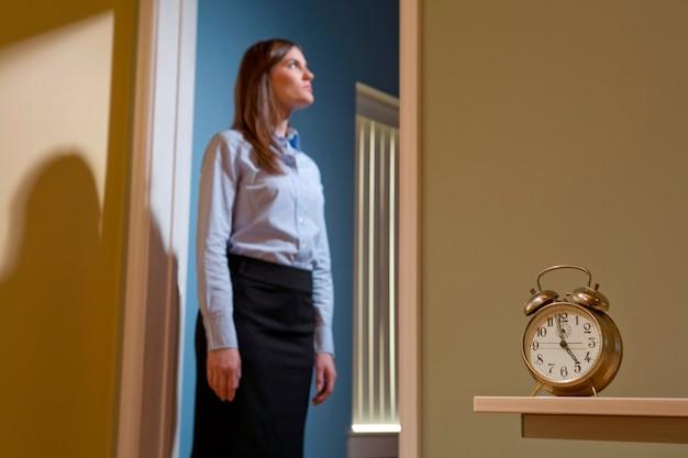 Jovem, femininas, trabalhador escritório, ficar, entrada, focalize alarme, relógio, em, a, primeiro plano