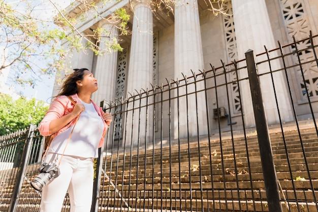 Jovem, femininas, turista, carregar câmera, sobre, ombro, olhar, predios, cidade