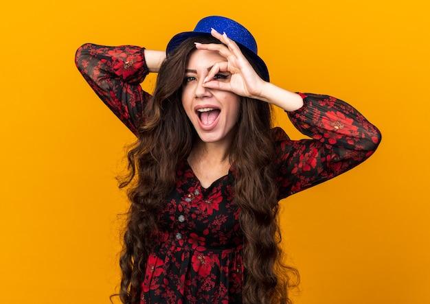 Jovem festeira impressionada com chapéu de festa olhando para frente fazendo gesto de olhar com a mão na cabeça isolada na parede laranja