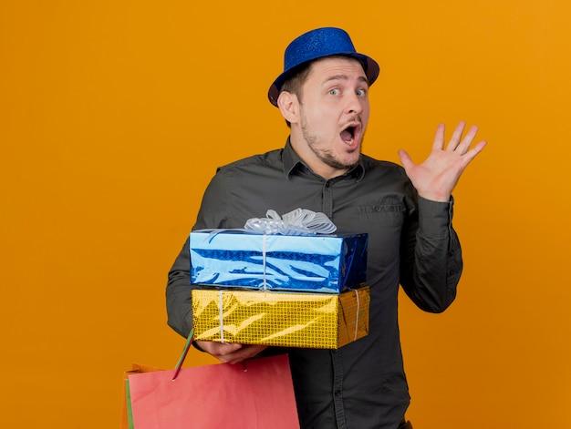 Jovem festeiro com medo de usar um chapéu azul e segurando uma caixa de presente com uma bolsa espalhando a mão isolada em uma laranja