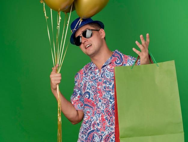 Jovem festeiro descontente com chapéu azul e óculos, segurando balões com uma sacola de presente e espalhando a mão isolada no verde
