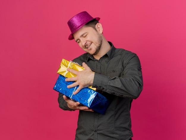 Jovem festeiro satisfeito com os olhos fechados e usando um chapéu rosa abraçando caixas de presente isoladas em rosa Foto gratuita
