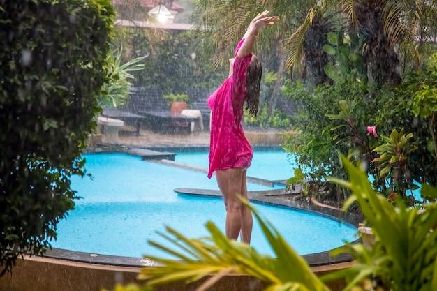 Jovem fica ao lado de uma piscina tropical ao ar livre na chuva.