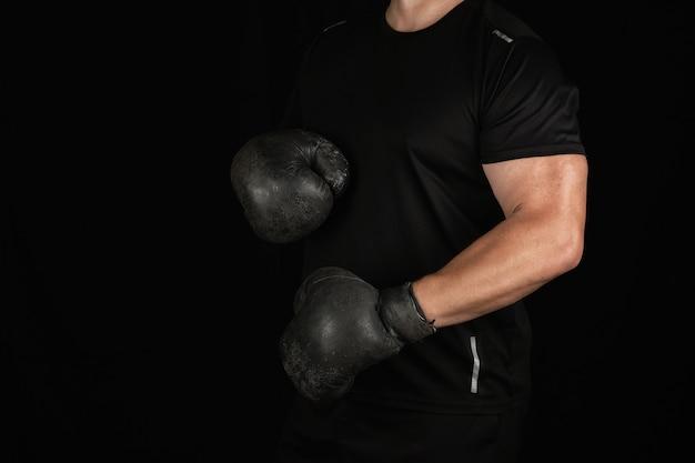 Jovem fica em um rack de boxe, vestindo muito velhas luvas de boxe pretas vintage