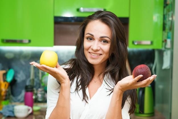 Jovem fica na cozinha segurando frutas nas mãos, garota caucasiana em uma cozinha moderna detém g ...