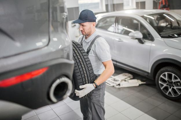Jovem fica na frente do porta-malas e segure o pneu com as duas mãos. ele olha com seriedade. carro branco está atrás dele.
