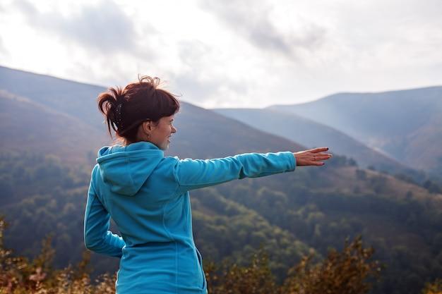 Jovem fica no topo e olhando para as montanhas.