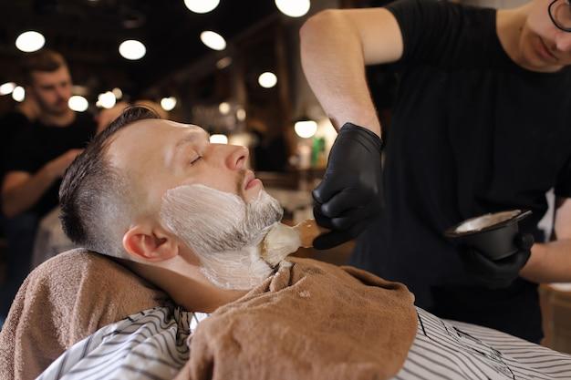 Jovem, ficando um barbear à moda antiga com navalha