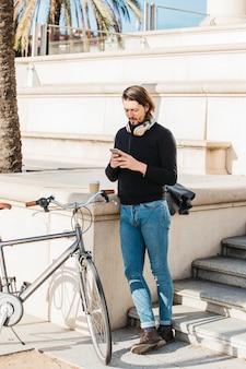 Jovem, ficar, perto, seu, bicicleta, usando, smartphone