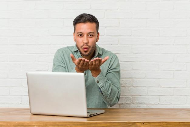 Jovem filipino sentado trabalhando com seu laptop, dobrando os lábios e segurando as palmas das mãos para enviar beijo no ar.