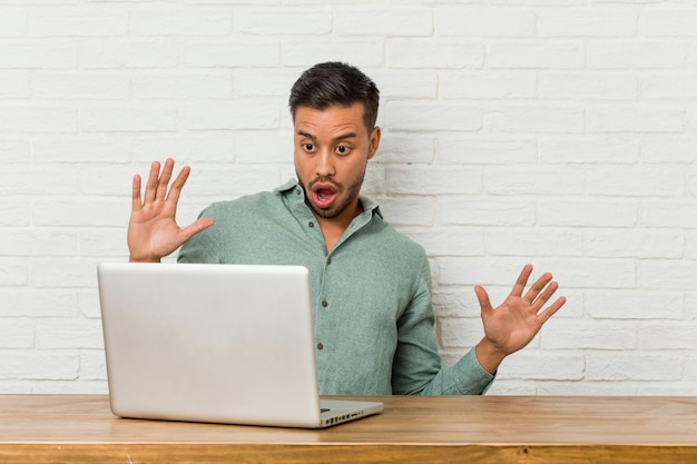 Jovem filipino sentado trabalhando com seu laptop sendo chocado devido a um perigo iminente