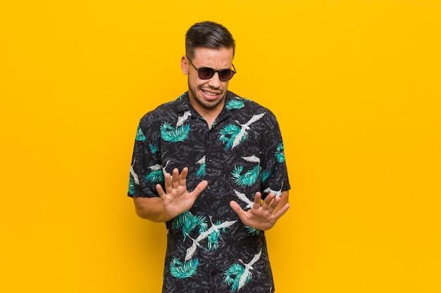 Jovem filipino vestindo roupas de verão, rejeitando alguém mostrando um gesto de nojo
