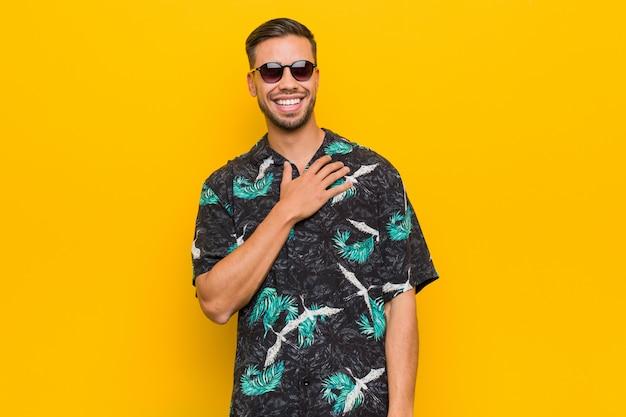 Jovem filipino vestindo roupas de verão ri alto, mantendo a mão no peito.