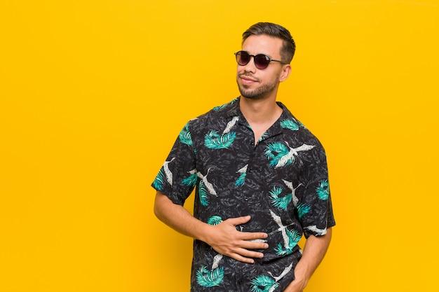 Jovem filipino vestindo roupas de verão toca a barriga, sorri suavemente