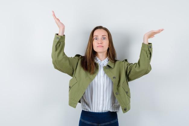 Jovem fingindo apresentar ou levantar algo na camisa, jaqueta e parecendo perplexa. vista frontal.