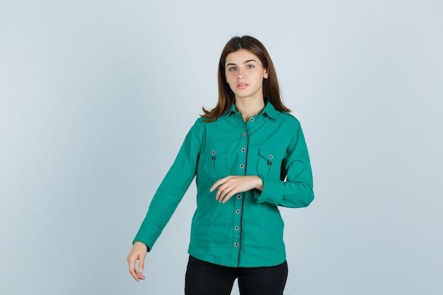 Jovem fingindo mostrar algo em seu lado direito em uma camisa verde e olhando perplexa, vista frontal.